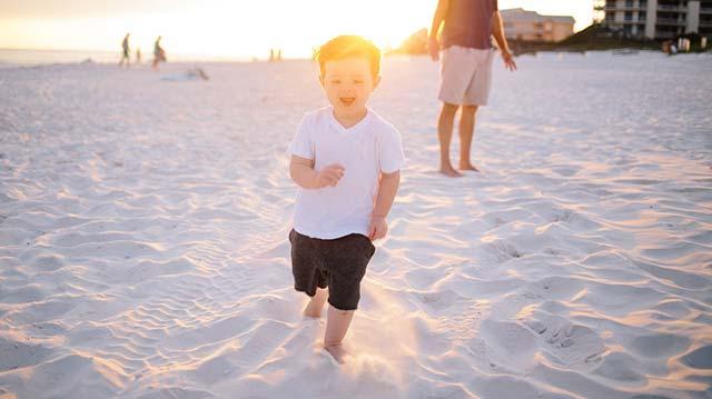 裸足で砂浜を歩く子供